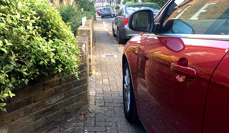 A car blocks part of a footpath, beside a wall